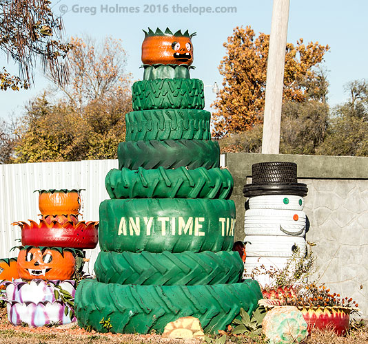 A tree and snowman made of tires regard motorists at for Snowmen made from tires